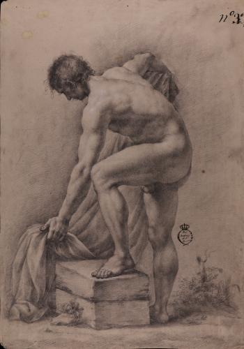 Estudio de modelo masculino desnudo con el pie izquierdo sobre un bloque semi agachado cogiendo un paño