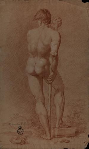 Estudio de modelo masculino desnudo de espaldas con vara y el pie derecho apoyado sobre un bloque